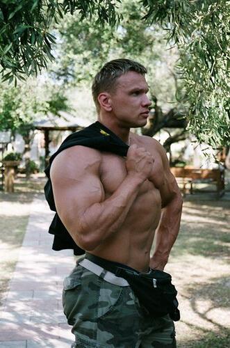Tシャツを肩にかけているマッチョな男性