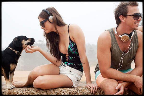 浜辺でヘッドホンをしているカップル