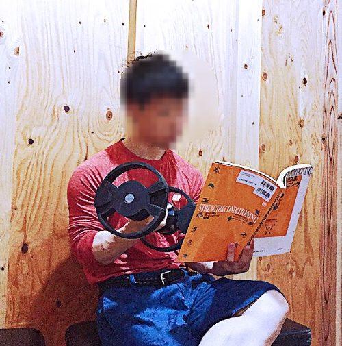 本を読みながら片手でダンベルを持ち上げるスズキツバサ